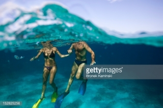 152825256-man-and-woman-hold-hands-in-clear-blue-water-gettyimages